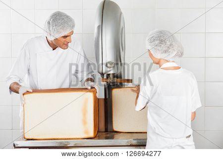 Baker's Using Cutting Machine In Bakery