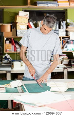Mature Worker Cutting Paper In Factory