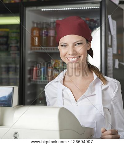 Saleswoman At Checkout Counter In Grocery Store