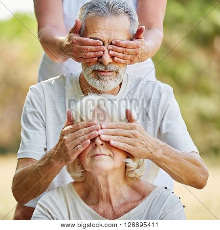 Seniors covering each other eyes from the back in the garden in summer