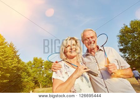 Happy senior couple while playing badminton in summer