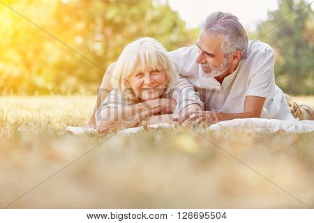 Two senior citizens relaxing in summer in the garden on a blanket