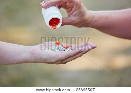 Person pours tablets from a pill package on an open hand
