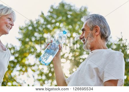Senior citizens drinking from a water bottle for refreshment in summer