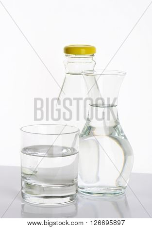 bottle, carafe and glass of fresh water on white background