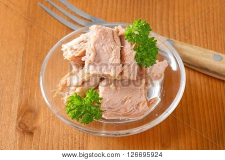 bowl of canned tuna with parsley on wooden table