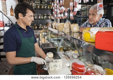 Man Talking With Salesman Slicing Cheese In Shop