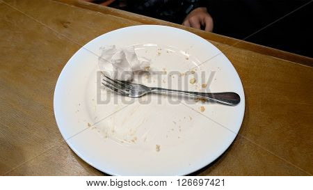 Person finished to eat and put fork knife and napkin serviette on the empty plate. Cafe restaurant casual scene.