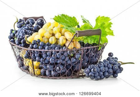 Basket blue and white grapes with green leaf. Isolated on background