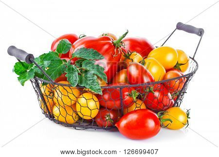 Basket red and yellow tomatoes from green leaf. Isolated on white background
