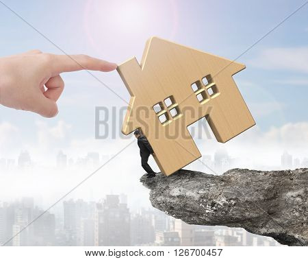 Man Holding Wooden House On Cliff Edge With Hand Pushing