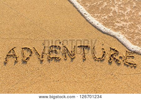 Adventure - inscription by hand on yellow beach sand.