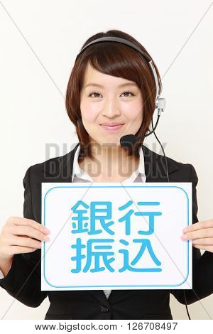 businesswoman holding a message board with the phrase bank transfer in KANJI
