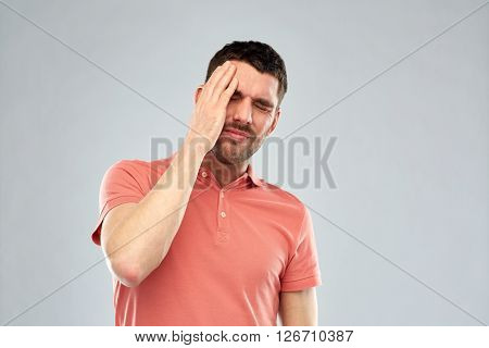 people, crisis, emotions and stress concept - unhappy man suffering from head ache over gray background
