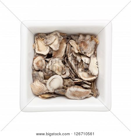 Traditional Chinese Medicine - Sliced notoginseng in a square bowl isolated on white background