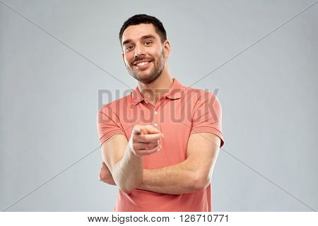 gesture and people concept - man pointing finger to you over gray background