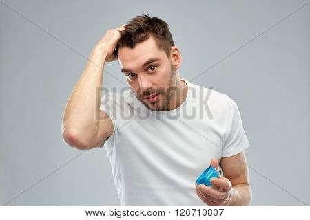 beauty, hairstyle, haircare and people concept - happy young man styling his hair with wax or gel over gray background