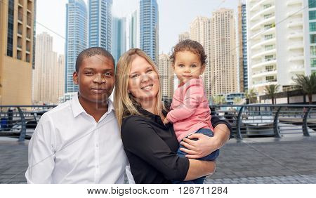 family, travel, tourism and international concept - happy multiracial mother, father and little child over dubai city street background