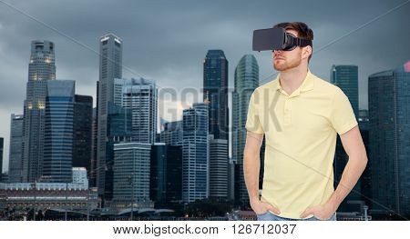 3d technology, virtual reality, travel, entertainment and people concept - young man with virtual reality headset or 3d glasses over singapore city skyscrapers background
