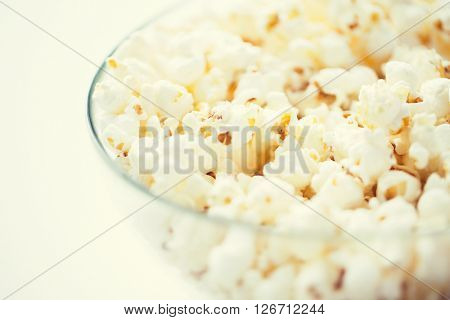 fast food, junk-food and unhealthy eating concept - close up of popcorn in glass bowl