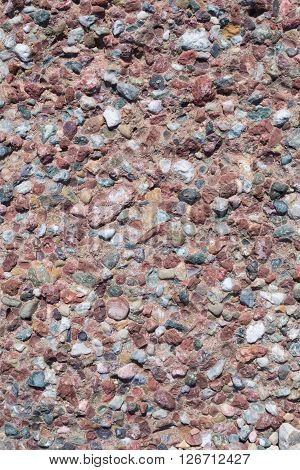 Stone texture. Portrait of a gray stone. Conglomerate with light stones. Vertical image.