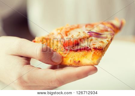 people, fast food, italian kitchen and eating concept - close up of hand holding pizza slice