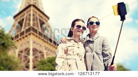 people, children, travel, tourism and technology concept - happy girls taking picture with smartphone on selfie stick over paris eiffel tower background