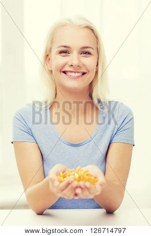 healthy eating, medicine, health care, food supplements and people concept - happy woman holding handful of fish oil capsules at home