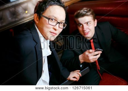 two stylish man talk, dressed in suits and ties in an informal atmosphere in the bar, the men's friendship.