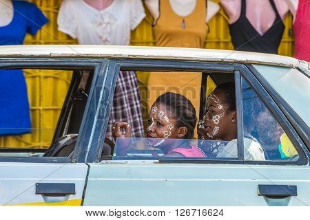 Hell Ville Madagascar - December 19 2015: Malagasy women of ethnicity Sakalava with traditional paint mask in the car on the background of female mannequins in Nosy Be island North of Madagascar.