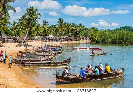 Ambatozavavy Nosy Be Madagascar - December 19 2015: Boaters on their traditional wood pirogue with outrigger waiting for passengers in the Ambatozavavy village on the island of Nosy Be Madagascar. Traditional fishing village on Nosy Be island with wooden