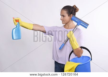 Portrait of attractive young woman with cleaning products gloves and bucket. Isolated white background.