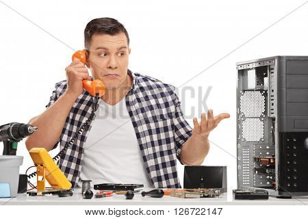 Confused PC technician talking on the phone isolated on white background