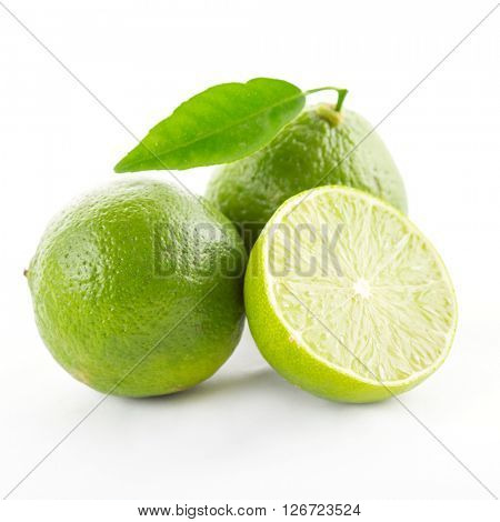 Lime with slices and leaves isolated on white background.