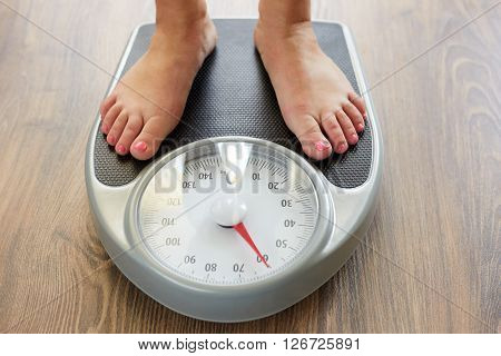 Female Bare Feet With Weight Scale On The Wooden Floor