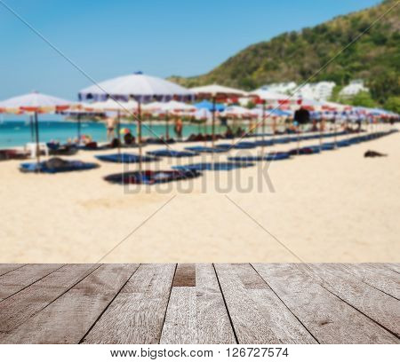 Wooden table top on blurred parasol and some people relax on the white sand beach and blue sea with blue sky background Can be use for display or montage your product