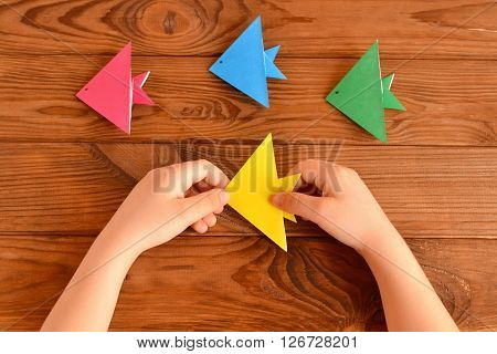 Child holds a origami fish. Set of colorful origami fish on a wooden table