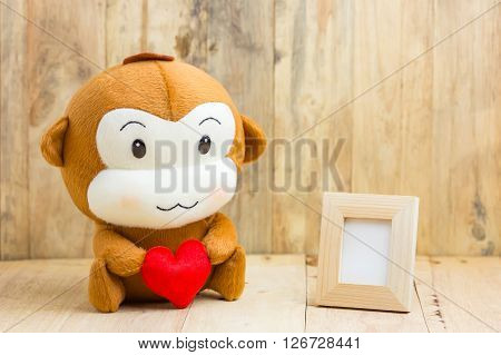 Happy Smiling Monkey Doll Hugging Red Heart With Picture Frame Sitting On Wood, Gift Of Love Concept