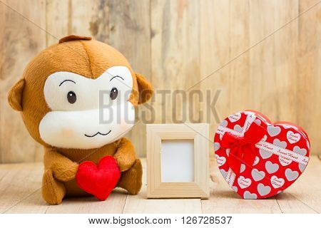 Happy Smiling Monkey Doll Hugging Red Heart With Picture Frame And Gift Box Sitting On Wood, Gift Of