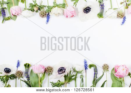 Pink tulips white anemones pink cloves and white buttercups lying on white background in two rows on top and on the bottom