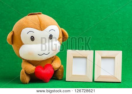 Happy Smiling Monkey Doll Hugging Red Heart, With Picture Frame Sitting On Green Background Gift Of