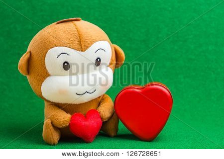 Happy Smiling Monkey Doll Hugging Red Heart, With Gift Box Sitting On Green Background Gift Of Love