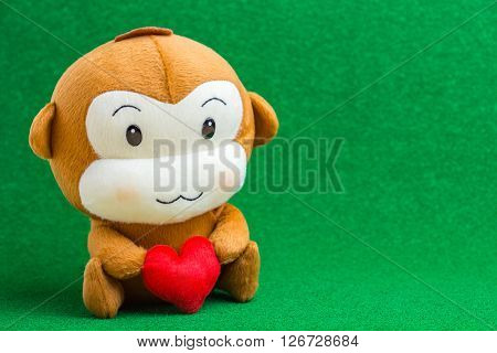 Happy Smiling Monkey Doll Hugging Red Heart, Sitting On Green Background Gift Of Love Concept