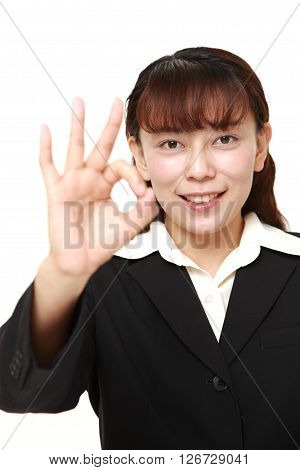 Asian businesswoman showing perfect sign on white background