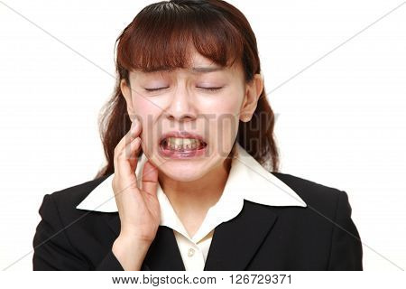 Asian businesswoman suffers from toothache on white background