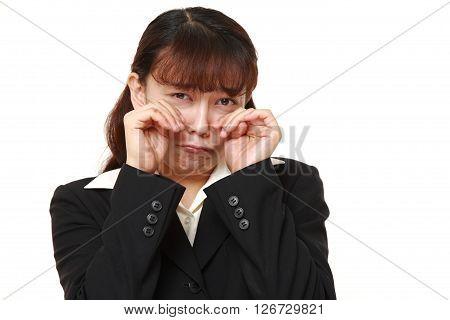 studio shot of Asian businesswoman cries on white background