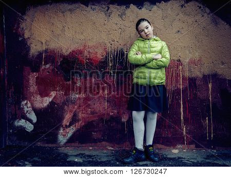 Sullen teen girl standing at the grunge wall