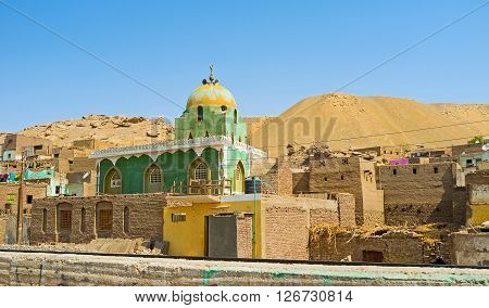 The bright green mosque in the Nagaa Al Khalasab surrounded by old houses and desert hills of Upper Egypt.