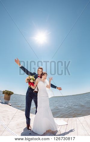 Happy Bride and Groom, Dancing Against Sunshine on a Beautiful Pier, Romantic Married Couple