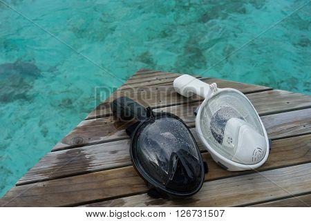 Black and white Snorkeling Mask on Dock at sea Maldives